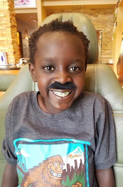 A smiling child with fake mustache and braces sitting in the dental chair at Senestraro Family Orthodontics in Wilsonville, OR.
