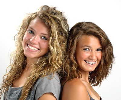Teenage girls smiling with braces at Senestraro Family Orthodontics.
