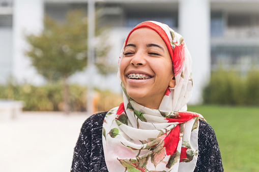 Teenage girl in colorful headscarf smiling with braces